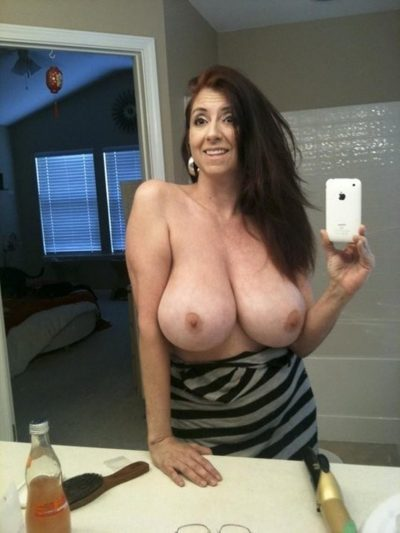 Fantastic busty mature taking selfshots of her perfect tits in bathroom mirror. Big boobed amateur takes nude selfie in the bathroom