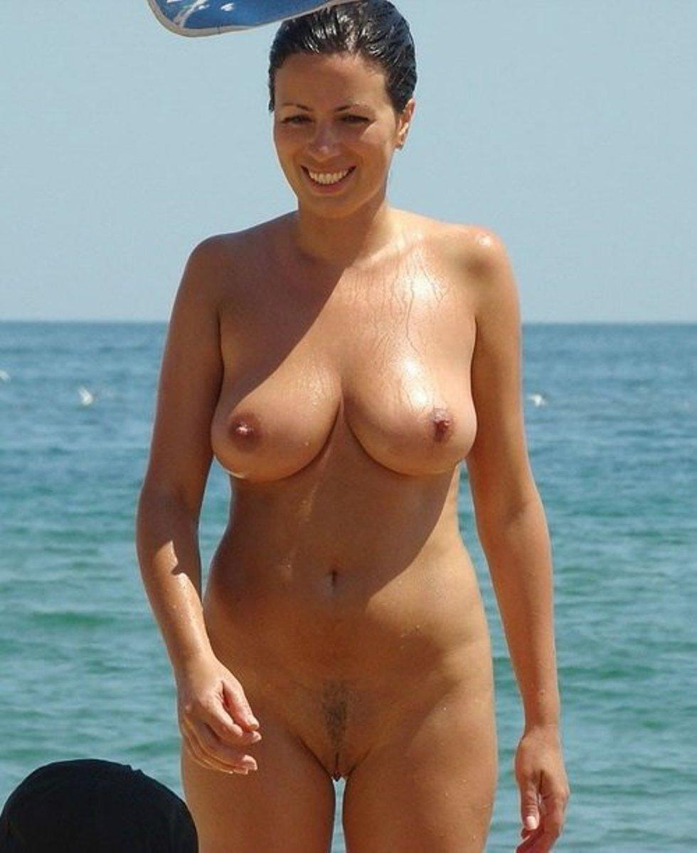 Sexy MILF chick strips in the beach to welcome the day with bare big tits. Hot Mom removes her swimsuit at the beach for centerfold shoot