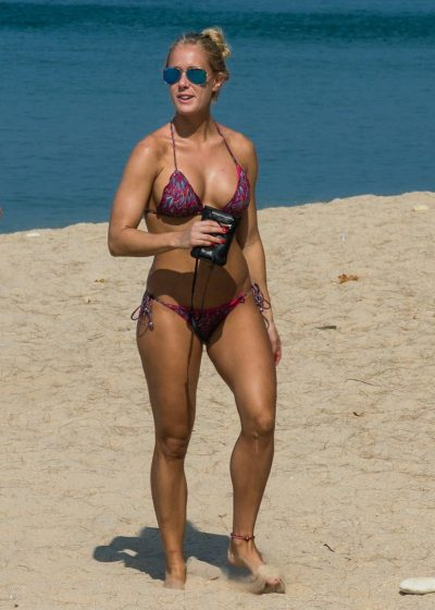 Athletic blonde MILF outdoors posing to show her fit body on the beach. Sexy muscle MILF in a skimpy bikini to beach it looks like a million dollars