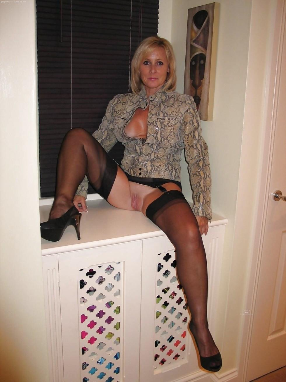 Naughty wife shows her meaty pussy and bares her sexy legs in stockings. Cheerful MILF strips her black lingerie to show her twat
