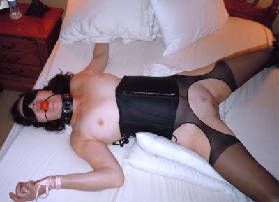 Mature brunette with shaved love holes posing nude and chained to bed. Collared sex slave nude wife is tied up and made to please her owner