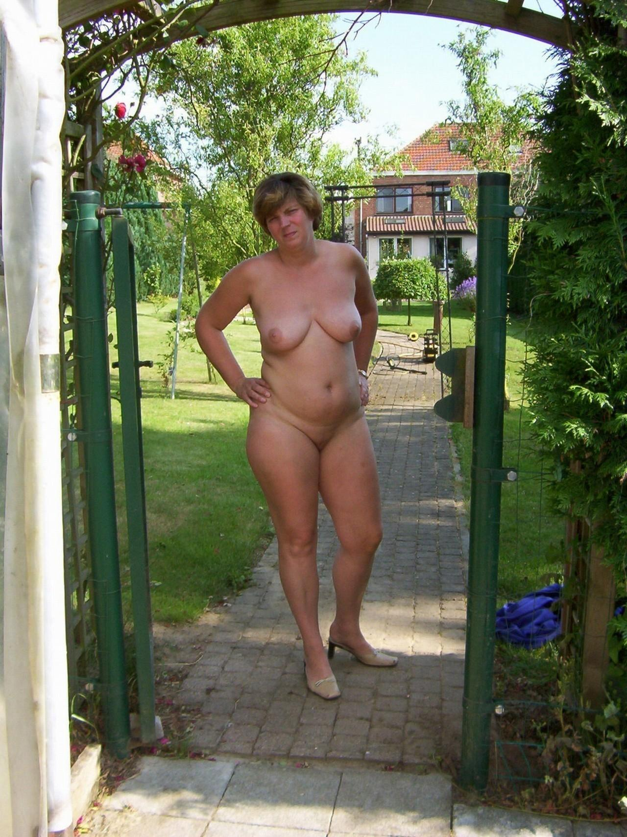 Seductive MILF lady with natural tits stripping in outdoor at the gate. Nude chubby cutie babe shakes her boobs and twat in the back yard