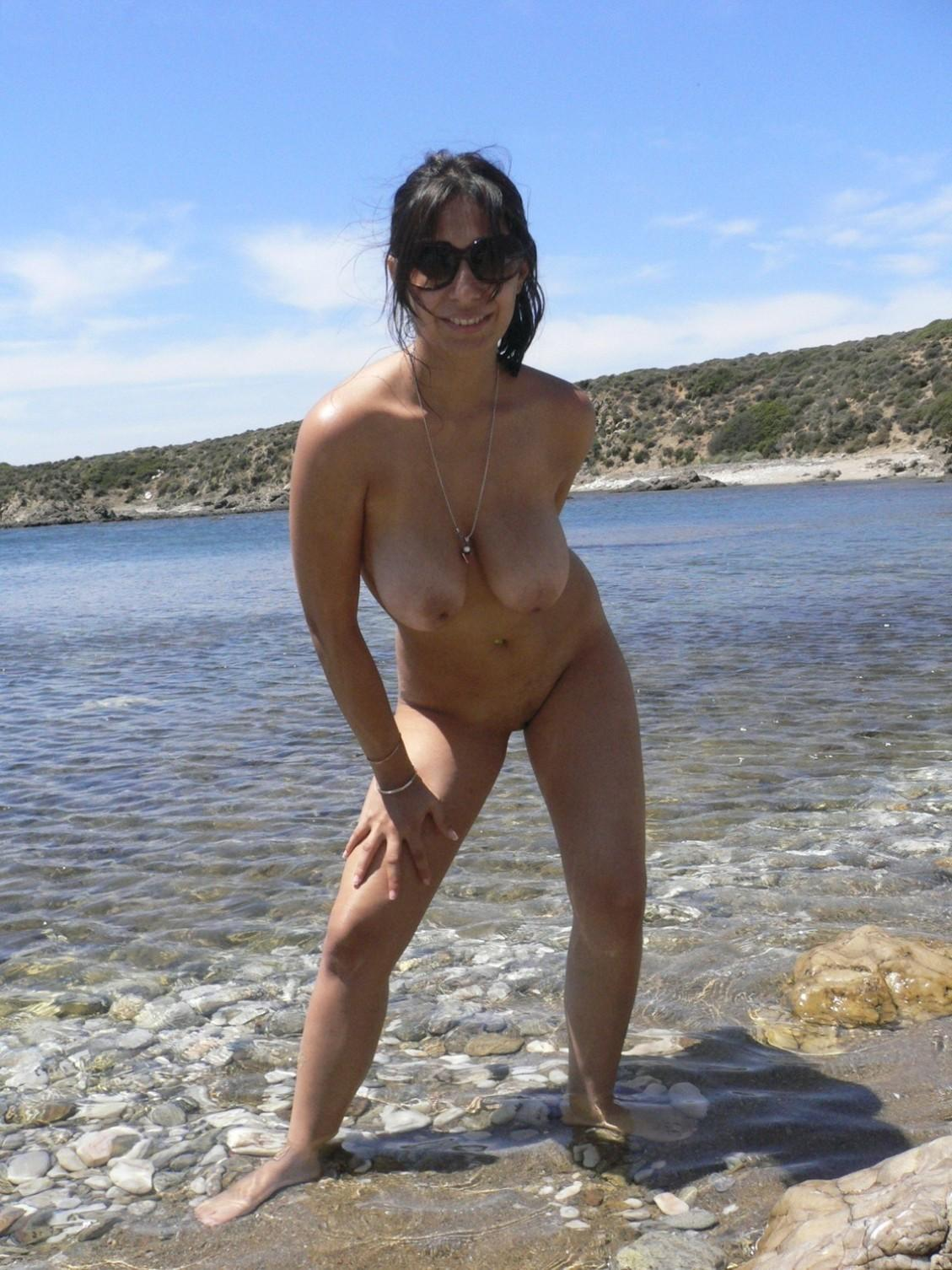 Italian amateur babe with a horny look and natural tits exposes her pussy on the beach. Nice Italian Milf removes her swimsuit after wading out into the sea