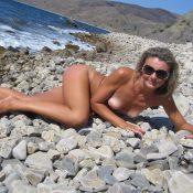 Graceful MILF blonde taking off her bikini and posing nude at the beach