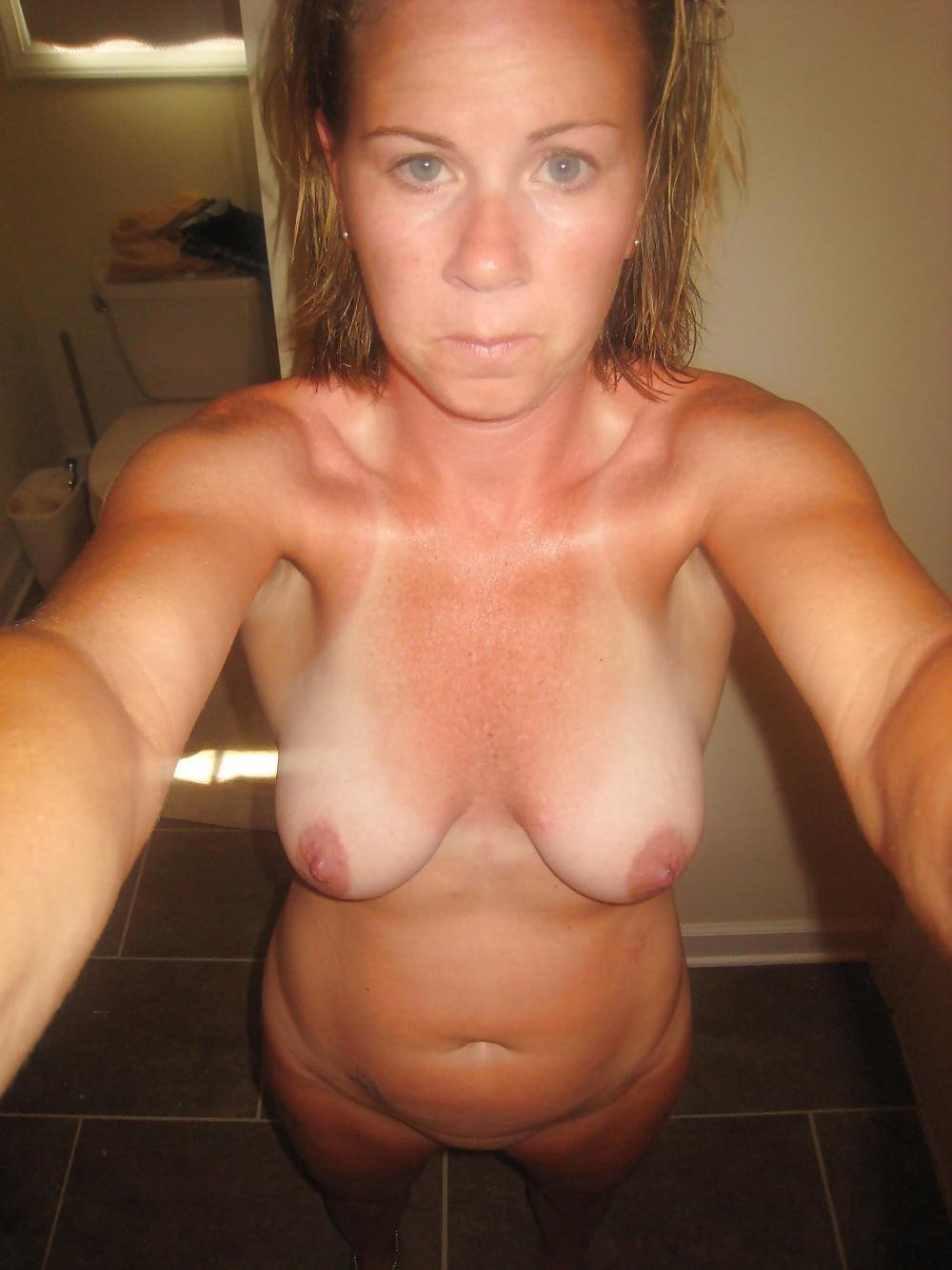 Naughty blonde wife taking naked bathroom selfie. Amateur MILF snapping selfies of her nice saggy tits