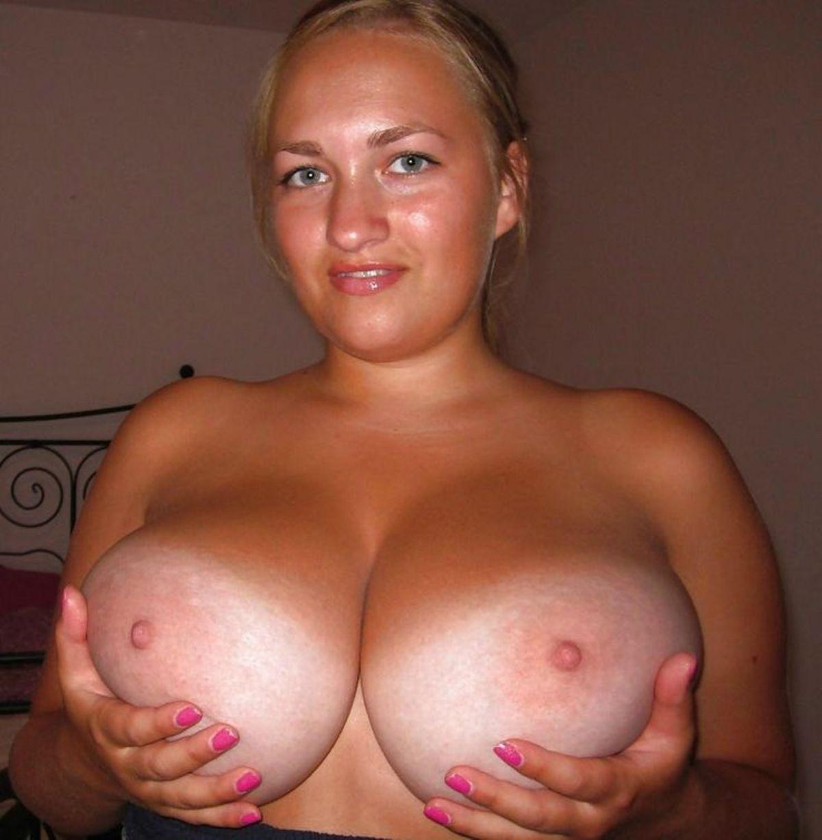 Busty female releases her big natural boobs from see thru dress. Hot MILF blonde shows naked big tits swing free