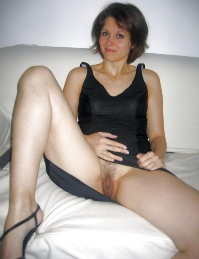 Naughty Milf showing off great legs and bald cunt in the nude picture. Beautiful brunette flashing hairy pussy lifting black dress