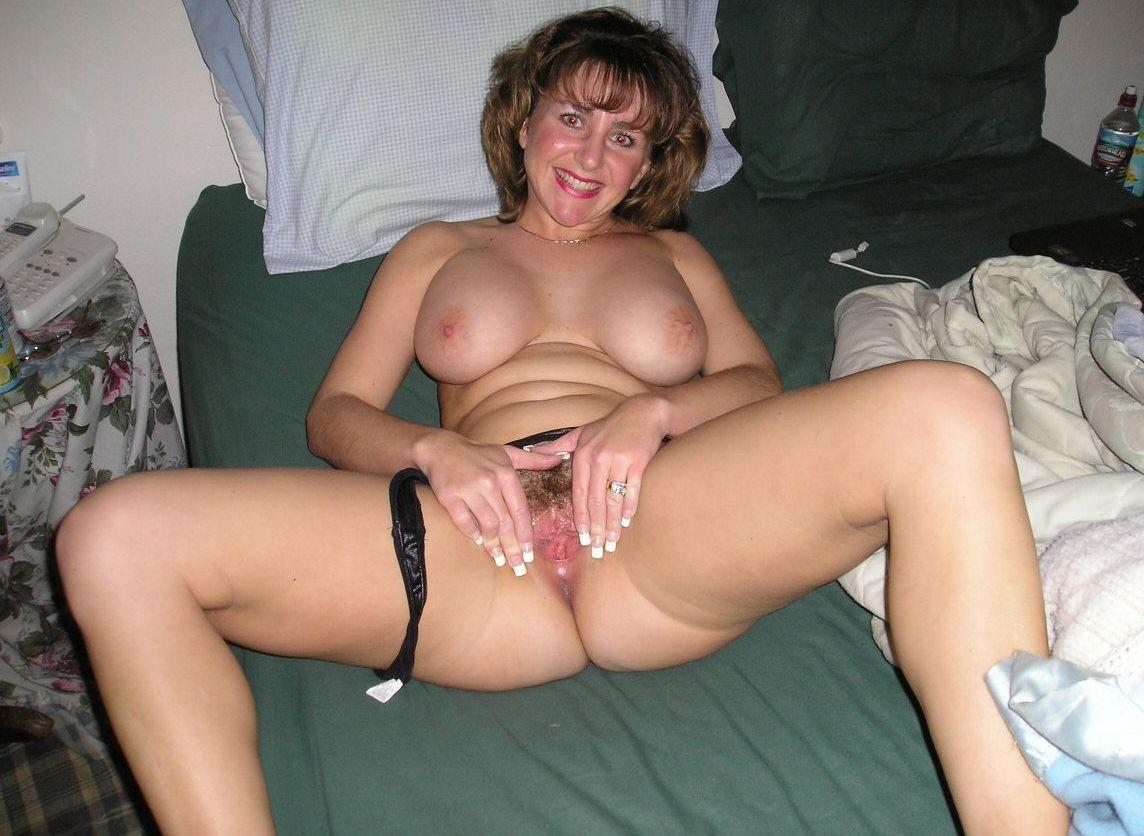 Mature wife shows big breasts & spreads naked on bedroom. Amateur Milf is the lucky owner of a hairy pussy