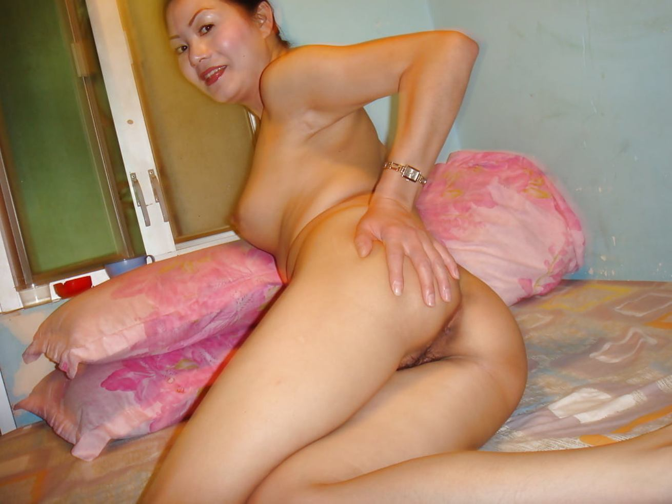 Mature asian slips off panties on her way to posing naked. Amateur Asian MILF shows her nude ass on xxx picture