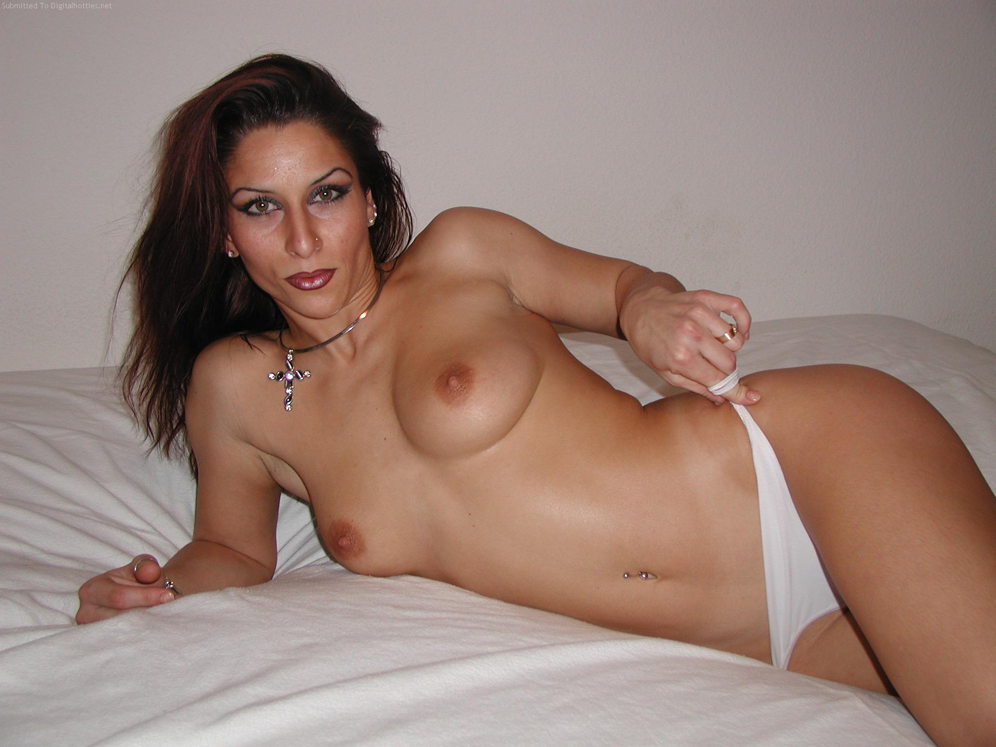 Amazing French MILF exposing her boobs lying on the bed. Brunette MILF lady flaunts her natural tits in nude picture