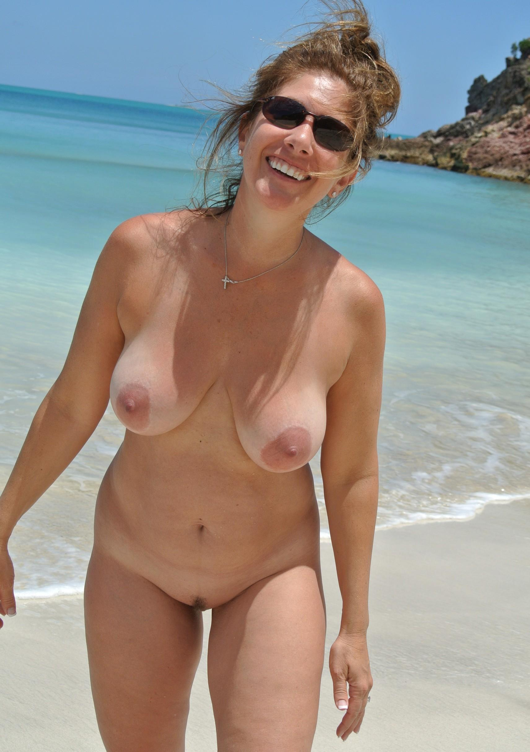 Nude busty MILF tanning her naked hot body on the beach. Hot wife letting her massive big tits hang loose at the beach