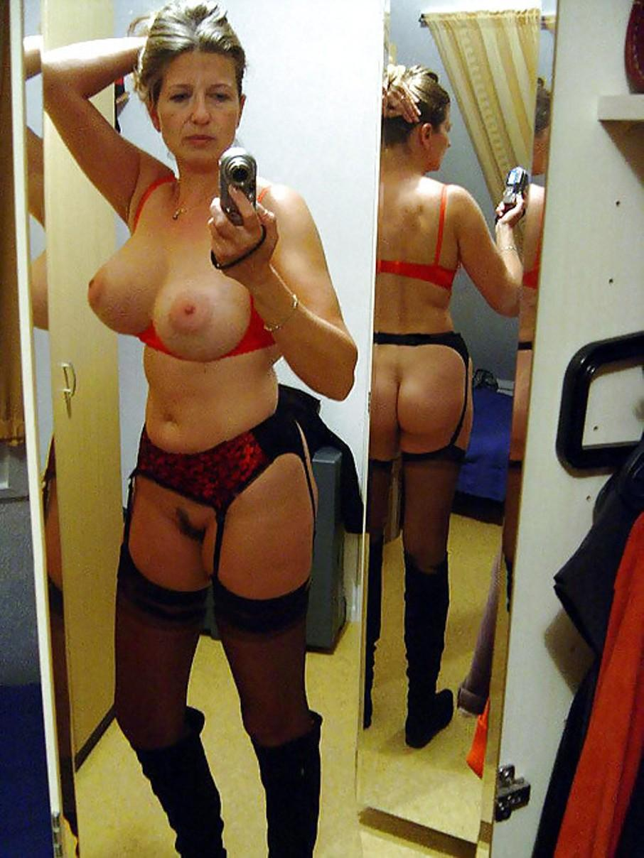 Mature blonde undressing to take selfie of her big tits. Amateur wife shows her great tits while taking mirror selfie