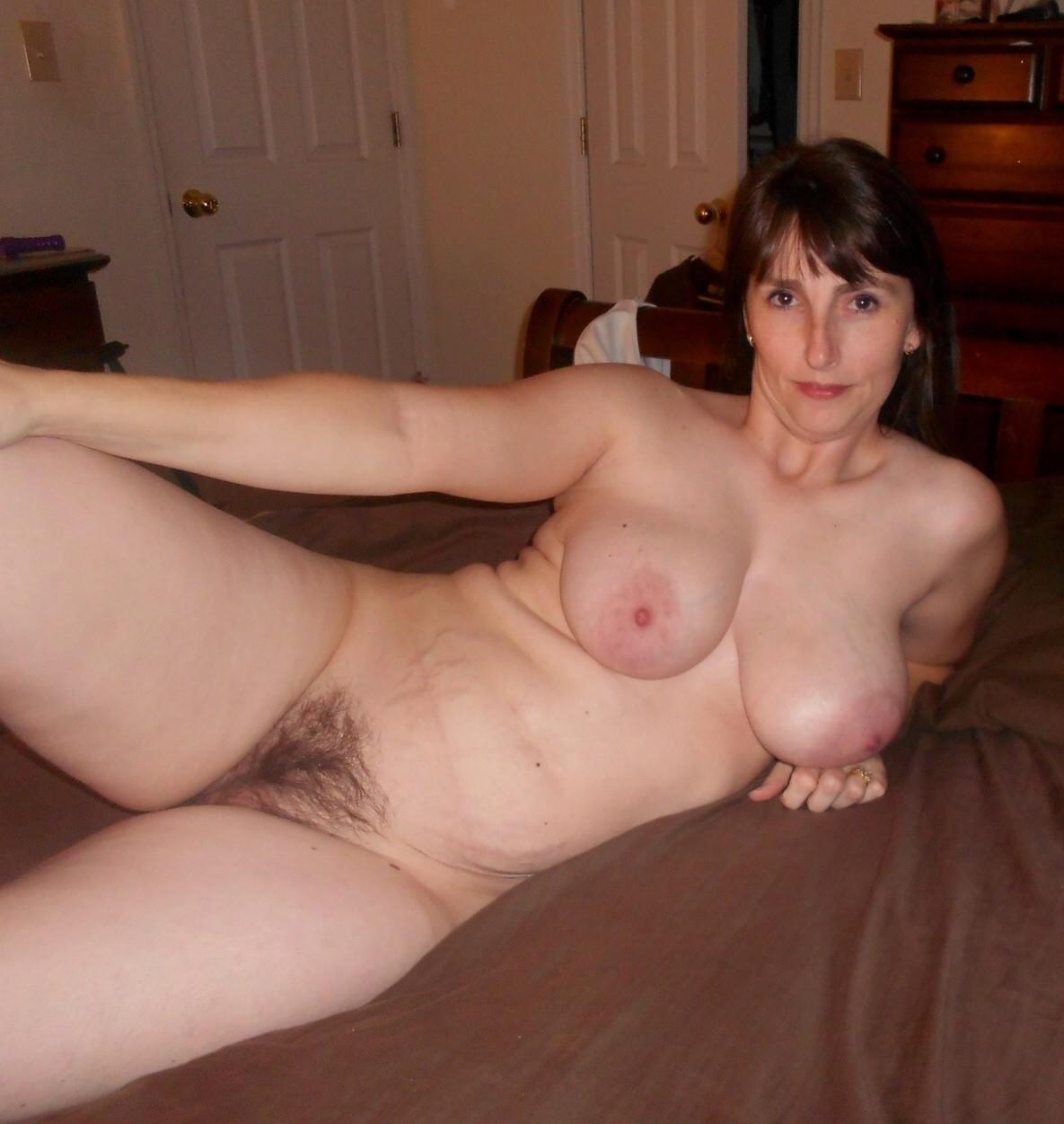 Nude amateur milf uncups her great tits before exposing her bush twat. Amateur mature proudly displays her hairy pussy in the nude