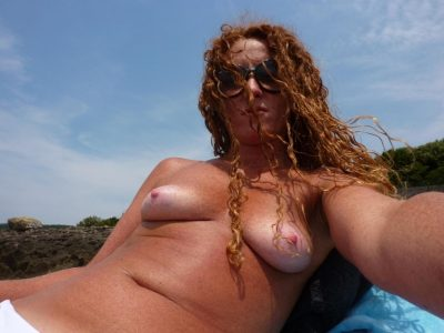 Hot redhead milf taking topless selfie while tanning boobs on the beach. Redhead wife freeing small tit from swimsuit before taking selfie