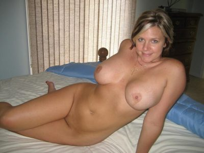 Cheerful blonde MILF with big natural tits strips naked on the bedroom