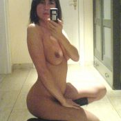 Nude Cougar brunette taking self shot in mirror