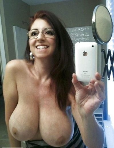 Glasses mature takes a self shot of her enticing great big tits. Amateur old lady takes nude selfie in mirror of her huge breasts