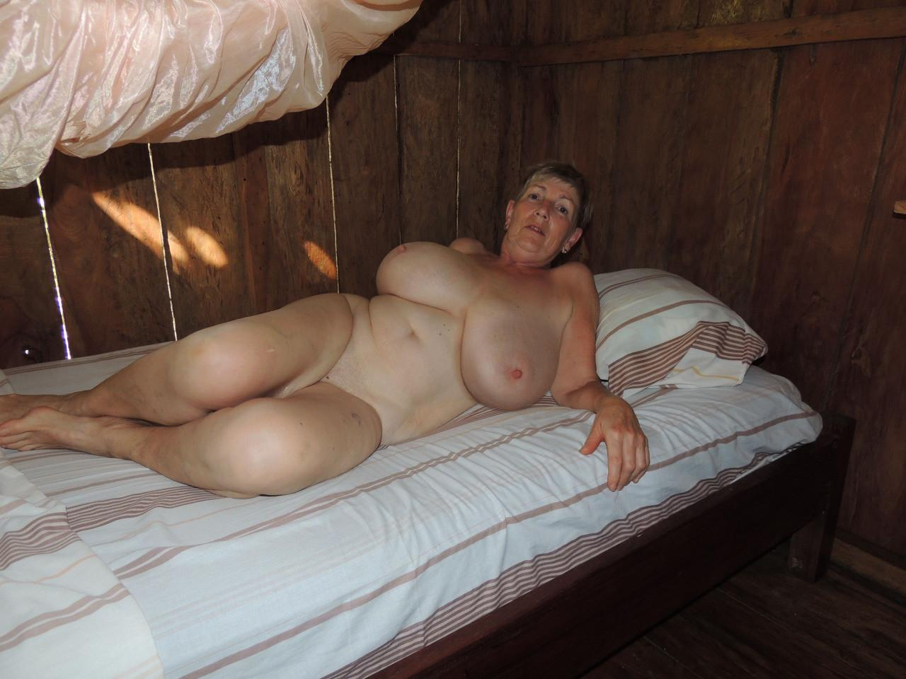 Nude granny show big natural tits. Fatty mature lady looks like a million dollars. Hot granny with big boobs strips and shows old pussy lying on the bed