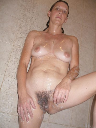 Mature uncovers her large tits and hairy pussy in the shower. Brunette old lady flaunting wet small tits & spreading bush cunt in the shower