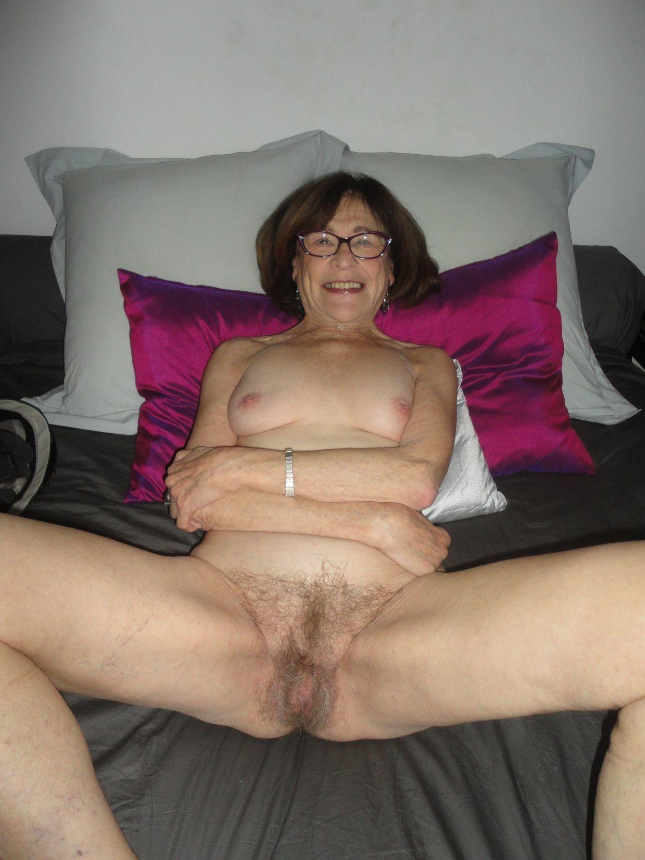 Mature granny in glasses reveals nice tits & a hairy pussy in the bedroom. Slender grannie spreading legs & posing naked