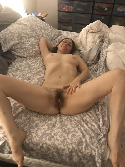 Naked mom demonstrating nice melons and bush cunt lying on the bed. Amateur MILF spreads her really hairy pussy wide open
