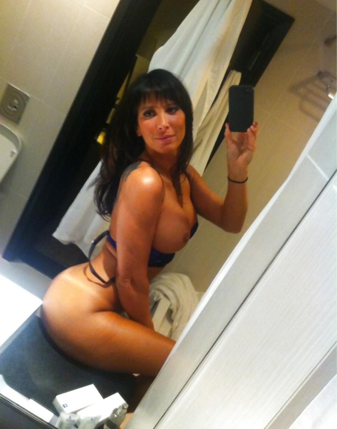 Big titted MILF flashing her big breasts and athletic figure in self shot. Pouty brunette beauty bares her great big tits for nude selfie