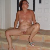 Mature woman spreads naked on the stairs