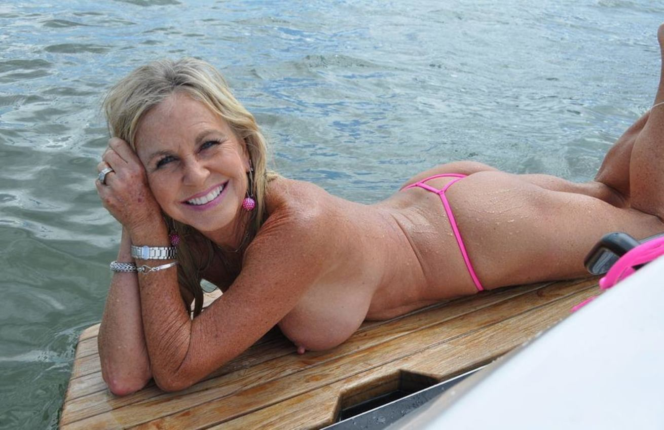 Sexy mature removes her bikini to get naked on the lake. Thick mature woman offs skimpy bikini flaunt her big tits