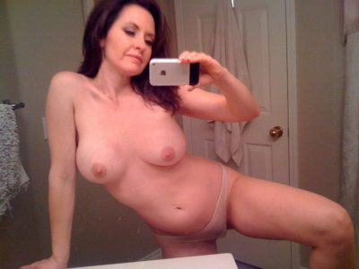 Amateur brunette MILF snapping selfie picture of her nice tits in mirror. Sexy mature women takes selfie of her natural tits in bathroom mirror