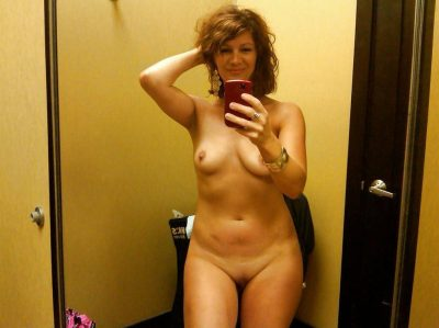 Amateur Housewife taking self shots in mirror while stripping naked. Brunette MILF with small titted takes naked selfie in mirror