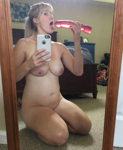 Nude blond Mom takes selfie while playing with sex toy. Wife takes picture of her naked body. Naughty MILF sucks on her vibrator while taking selfie