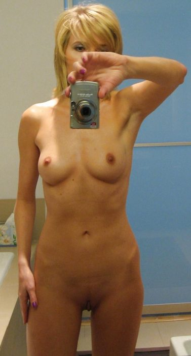 Skinny MILF takes self shot while removing her clothes. Mature taking selfie while getting naked. Beautiful wife looks stunning on her nude selfie photo