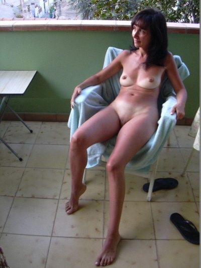 Slim older woman takes off panties to display her tan lined body in the nude. Milf wife with tiny tits shows tan lines sitting on a chair