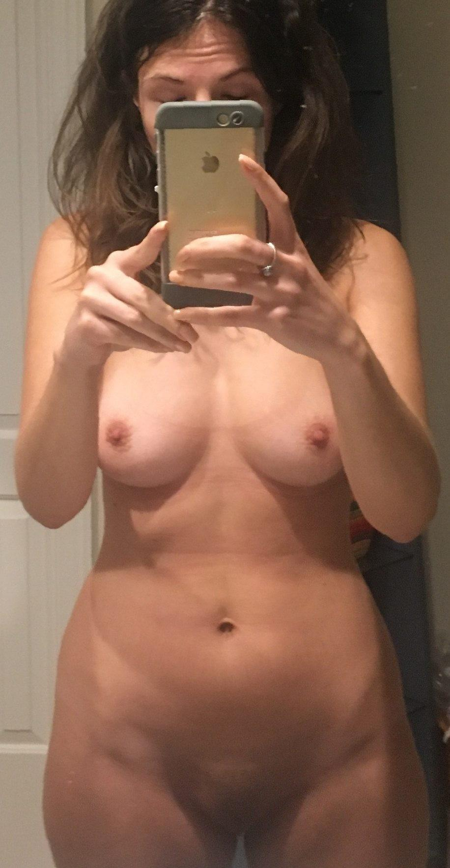 Nude selfie with a small tits belonging to a amateur MILF. Sweet wife takes selfie while exposing her small boobs and snatch