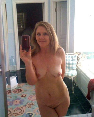 Older milf takes nude selfie while removing her clothes. Beauty wife with natural tits admires her naked body in a mirror