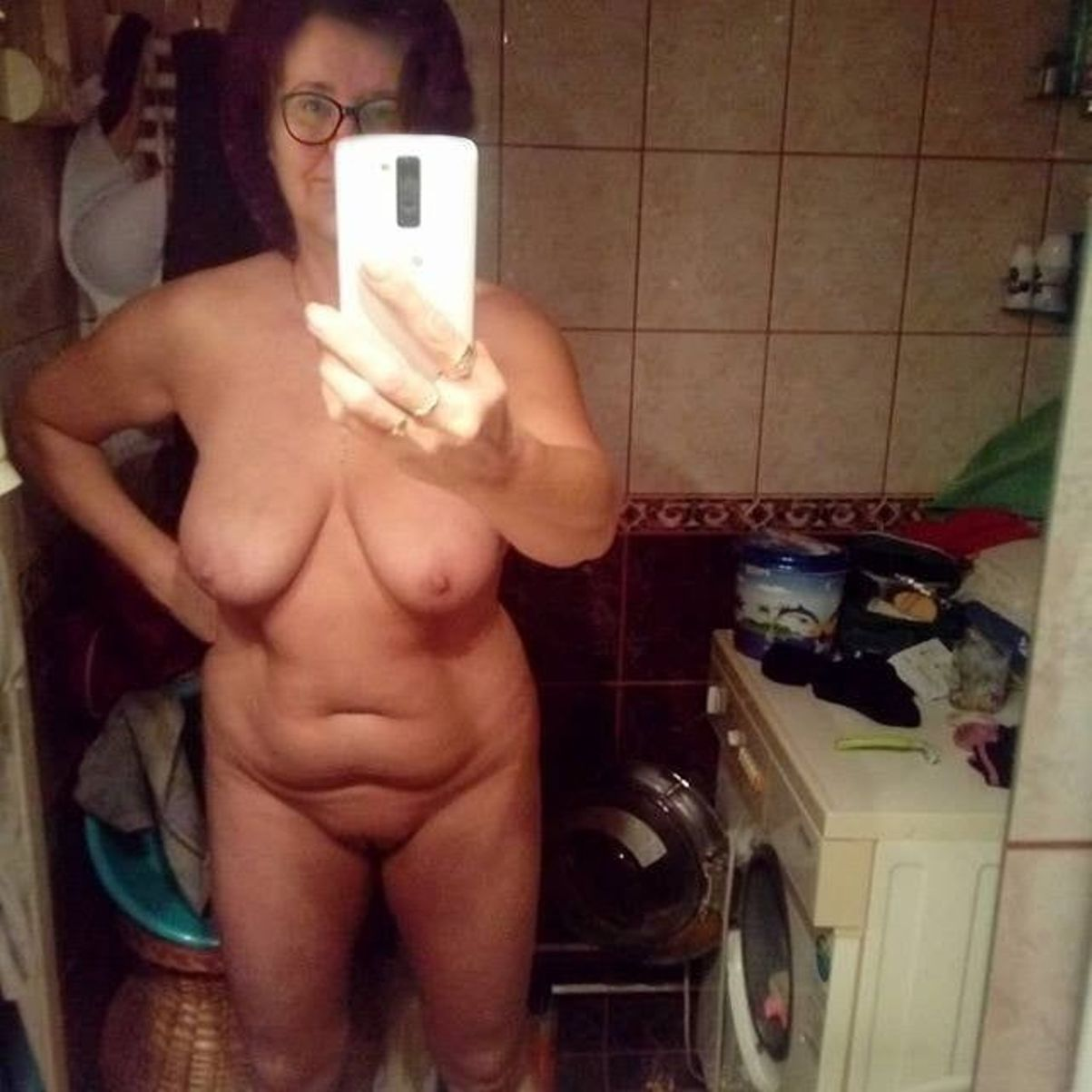 Chubby grannytakes totally naked selfie in the mirror. Glasses grandma with saggy boobs takes nude selfie