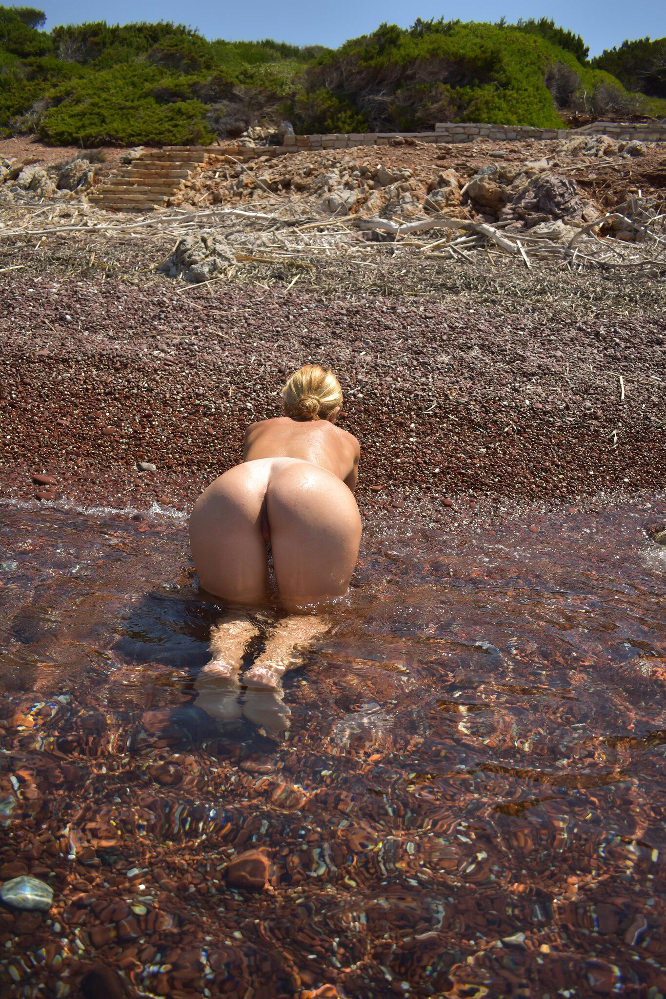 Curvy MILF likes showing off her hot big buttocks on the beach. Naughty mature nudist demonstrating juicy ass on the beach