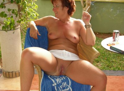 Redhead mom pierced nipples and vagina strips in the garden. Amateur wife smoking a cigarette spreads her pierced pussy sitting on armchair