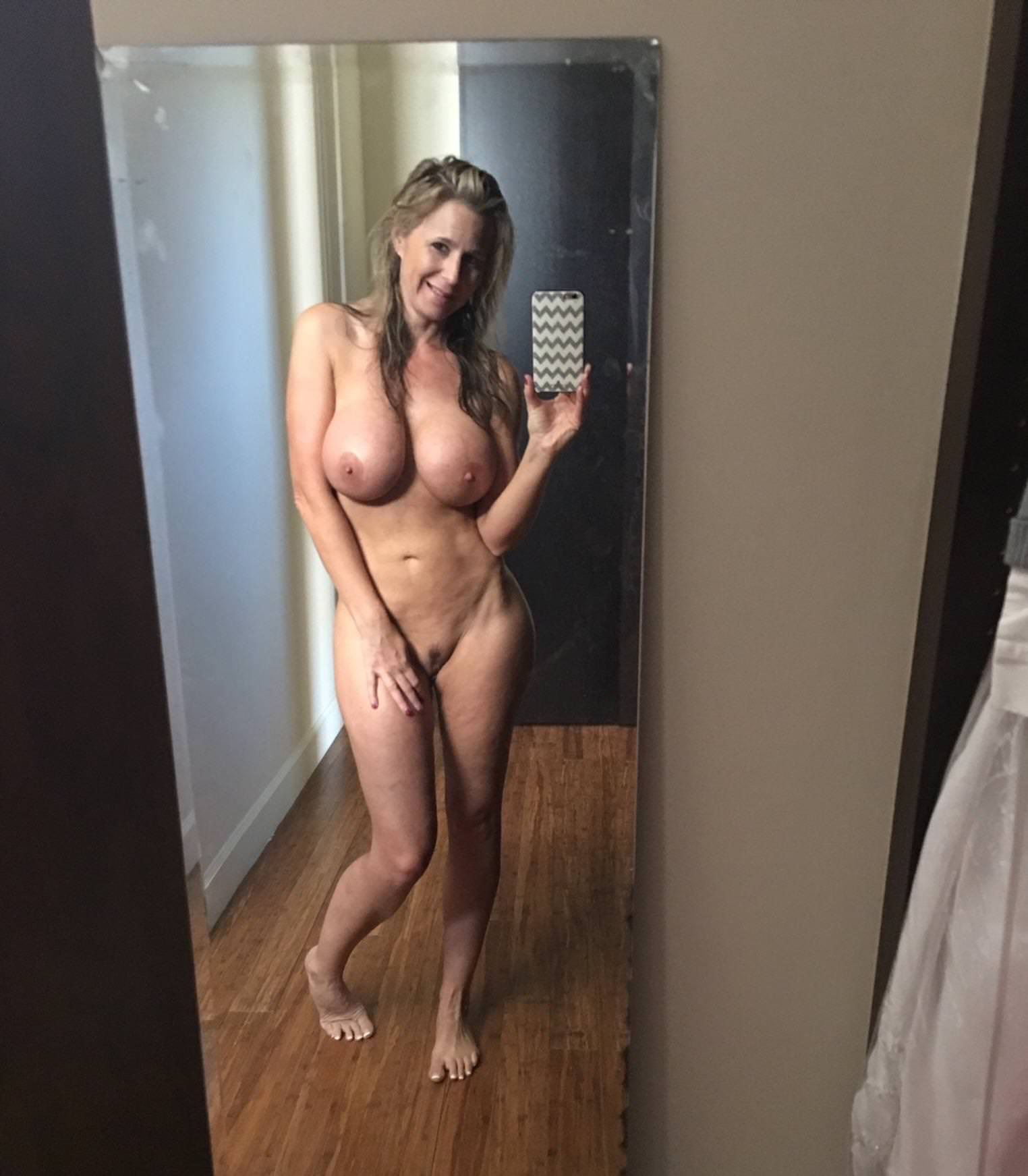 Gorgeous MILF takes selfie while showing nice tits and perfect body. Sexy blonde wife bares her big boobs during self shot action