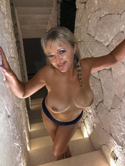 Busty MILF shows big breasts on the stairs. Blonde mature with large boobs stripping her clothes on the stairs