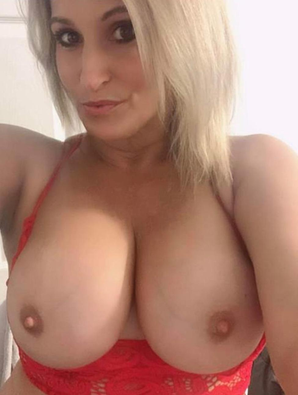 Charming amateur MILF with huge breasts stripping home alone. Perfect blonde female takes topless selfie displaying fantastic big boobs