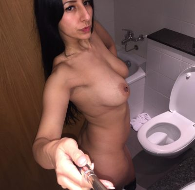Italian MILF takes selfies as she undresses on her bathroom. Sexy brunette amateur uncovers her huge tits and pierced nipples
