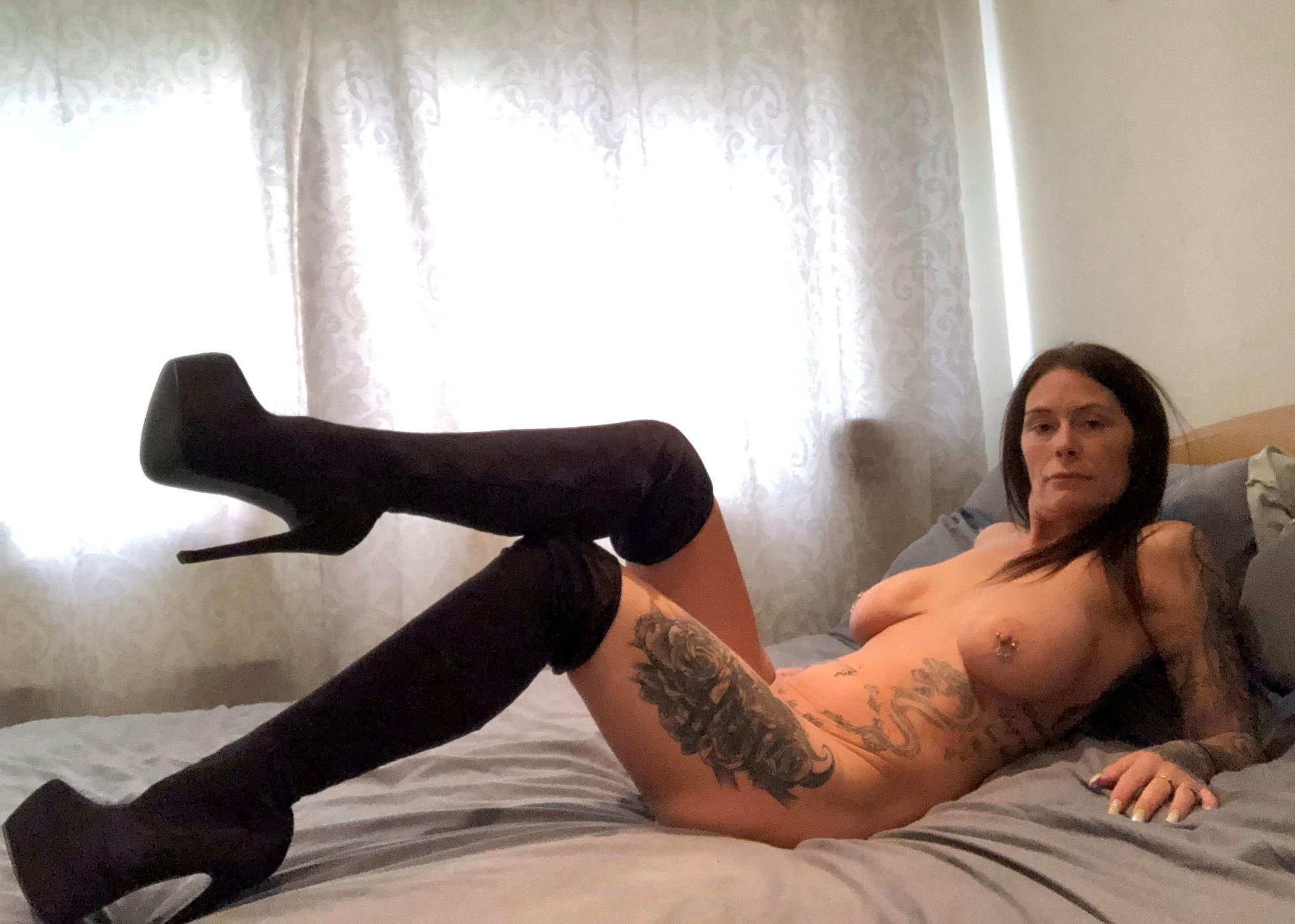 Naughty MILF strips to thigh high leather boots during solo action. Sexy hottie thigh boots showing off her round hot body lying on the bed
