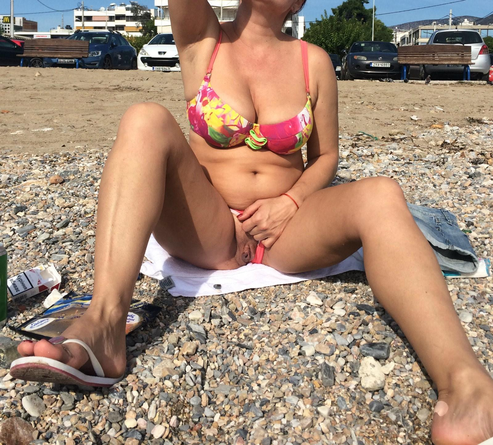 Russian MILF in a bikini showcases her smooth pussy on the beach. Old lady on the beach removes panty to show shaved pussy