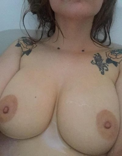Mom amateur bares her big round tits while taking a bath. Sexy female displays perfect breasts in a bathtub
