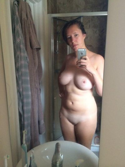 Nude housewife takes totally naked selfies in the mirror. Brunette MILF with a natural body is doing self shot in front of the bathroom mirror