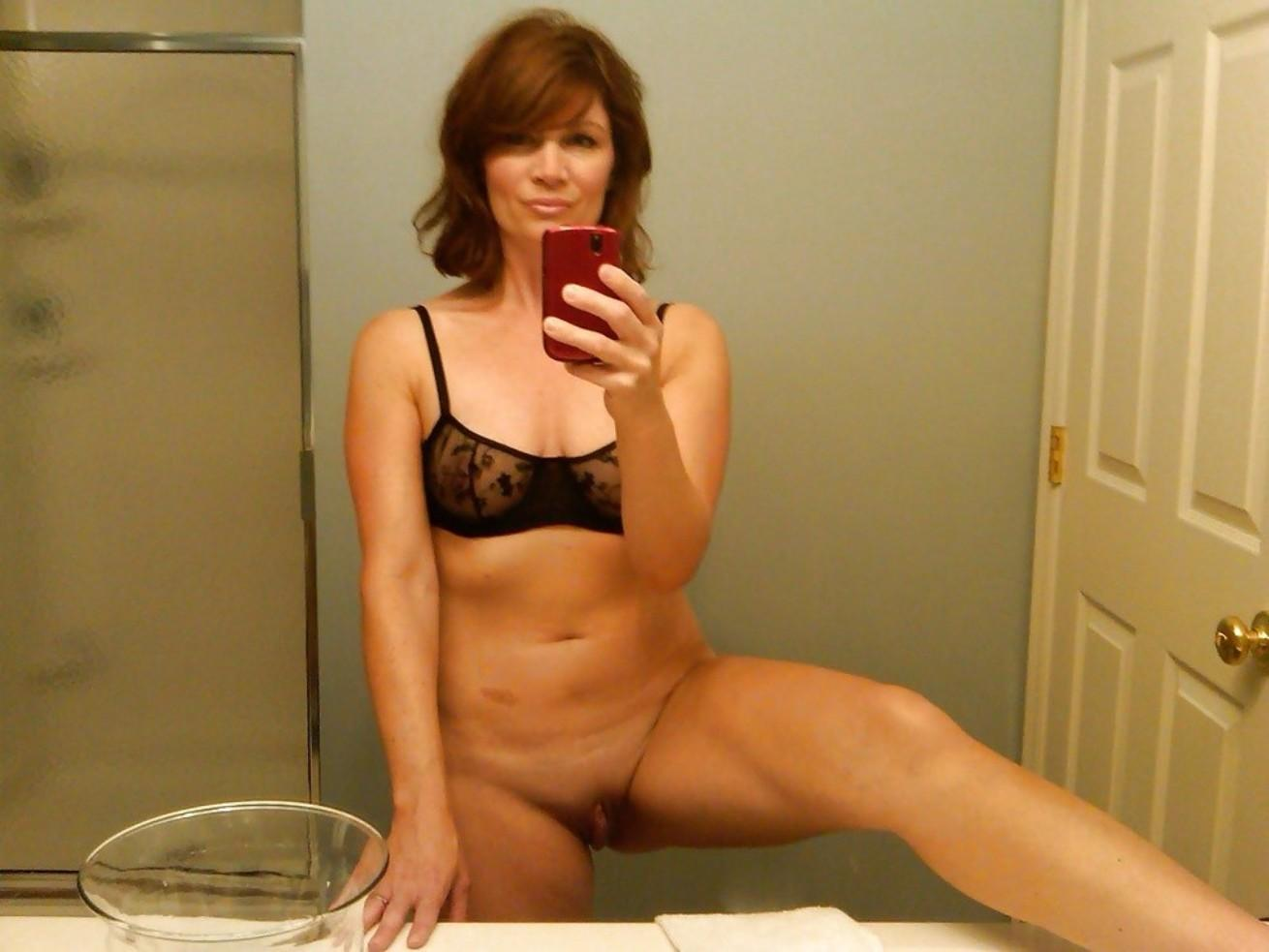 Awesome Milf without panties exposes a nice pussy in bathroom self shot. Mature babe takes pussy selfie in the bathroom mirror