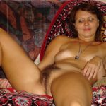 Russian MILF spreads her full bush while naked on bed. Nice wife from Russia poses naked on her bed after getting undressed