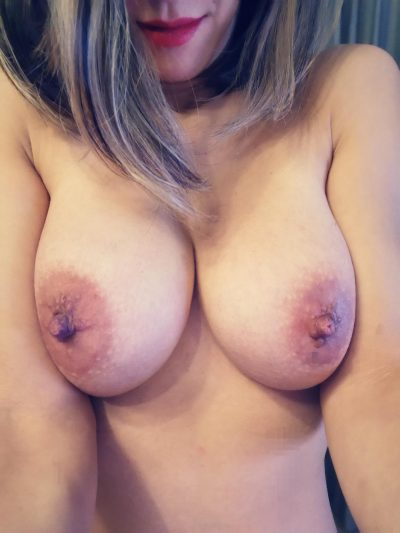 Sexy woman has red lips and perfect tits loves to brag. Amateur MILF takes a photo of her massive natural tits