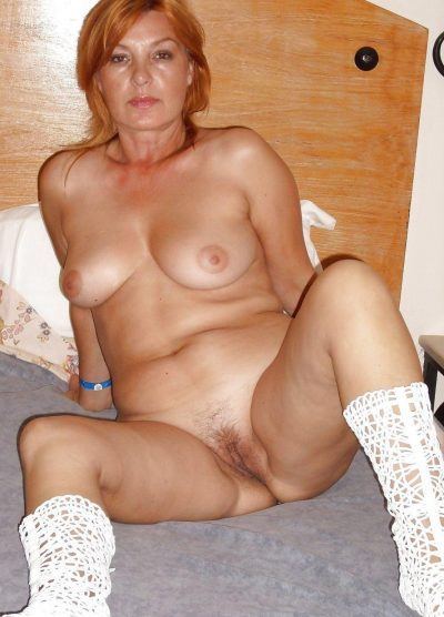 Redhead mature spreads her hairy pussy after removing a underwear. Sexy redhead amateur showcases her bush vagina while modeling naked